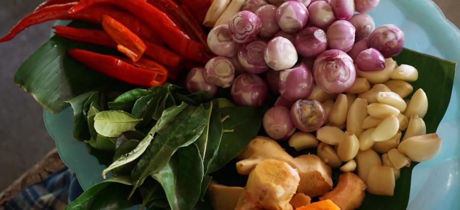 peeled shallots, garlic, galangal, turmeric and ginger roots, chilies, lemongrass, and bay leaves